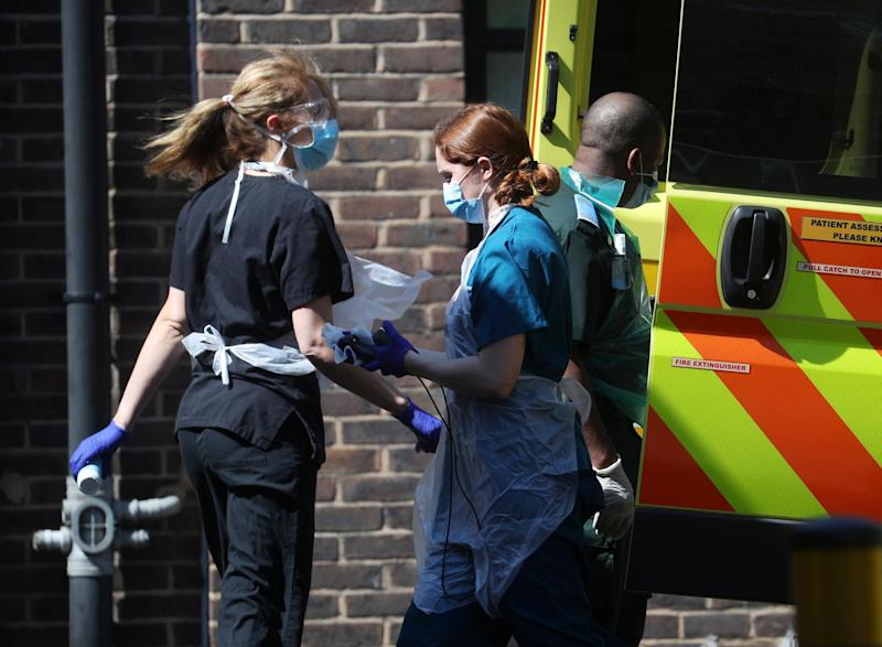 Medical staff wearing personal protective equipment (PPE) at the back of an ambulance outside Lewisham hospital: REUTERS