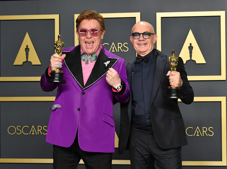 """HOLLYWOOD, CALIFORNIA - FEBRUARY 09: Musician Elton John and lyricist Bernie Taupin, winners of the Original Song award for """"'(I'm Gonna) Love Me Again,' Rocketman,"""" pose in the press room during the 92nd Annual Academy Awards at Hollywood and Highland on February 09, 2020 in Hollywood, California. (Photo by Amy Sussman/Getty Images)"""
