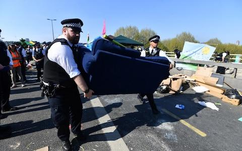 Police officers remove items used by Extinction Rebellion protesters from Waterloo Bridge - Credit: Paul Grover for the Telegraph