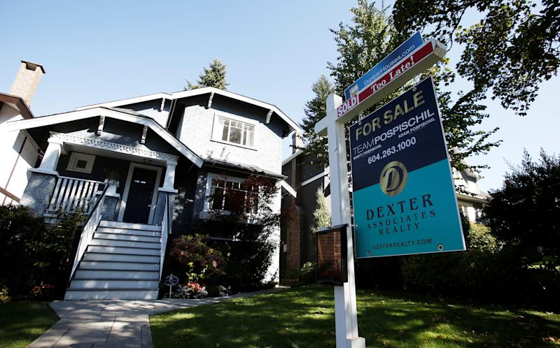 A real estate for sale sign is pictured in front of a home in Vancouver, British Columbia