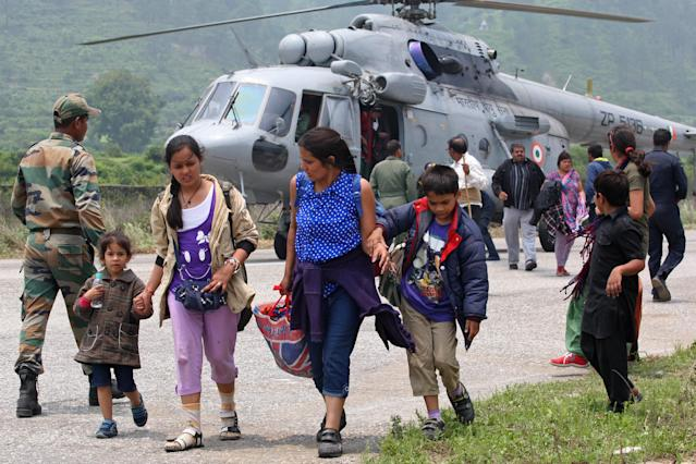 "In this handout photograph released by the Indian Ministry of Defence on June 23, 2013, rescued civilians from the Gangotri area walk away after being flown to safety on an Indian Air Force Mi-17 transport helicopter at Dharasu in Uttarakhand state on June 22, 2013. Bad weather hampered rescue operations June 23 in rain-ravaged northern India where the death toll from landslides and flash floods was likely to rise up to 1,000 with thousands of pilgrims and tourists still stranded in remote mountains without food or water for days. AFP PHOTO/MINISTRY OF DEFENCE/GURUDUTT MEHRA----EDITORS NOTE---- RESTRICTED TO EDITORIAL USE - MANDATORY CREDIT - ""AFP PHOTO/MINISTRY OF DEFENCE/GURUDUTT MEHRA"" - NO MARKETING NO ADVERTISING CAMPAIGNS - DISTRIBUTED AS A SERVICE TO CLIENTS -----"