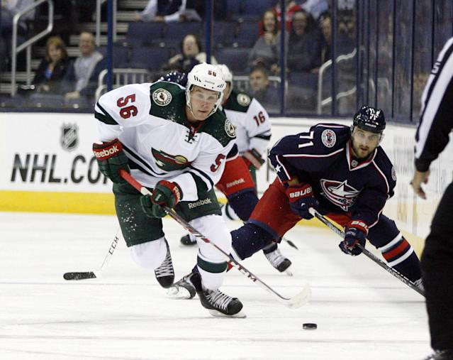 Minnesota's Erik Haula (56), of Finland moves the puck away from Columbus's Nick Filigno (71) in the first period of an NHL preseason hockey game, Monday Sept. 23, 2013 in Columbus, Ohio. (AP Photo/Mike Munden)