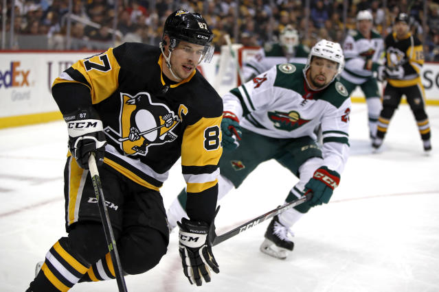 Pittsburgh Penguins' Sidney Crosby (87) works the puck in the corner with Minnesota Wild's Matt Dumba (24) defending during the second period of an NHL hockey game in Pittsburgh, Tuesday, Jan. 14, 2020. (AP Photo/Gene J. Puskar)