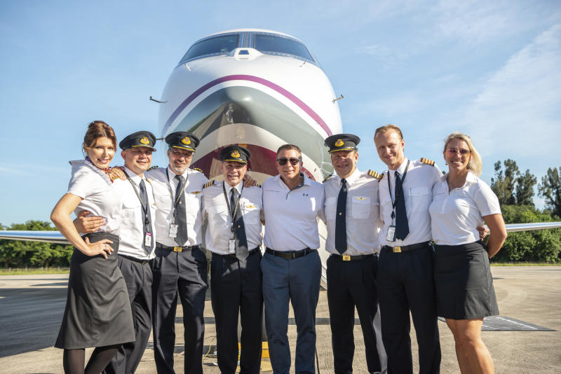 """In this Thursday, July 11, 2019 photo provided by Chris Garrison, Col. Terry Virts, former International Space Station commander, center with sunglasses, and British pilot Captain Hamish Harding, third from right, pose with other crew members in front of their Gulfstream aircraft after their record-breaking around-the-world flight over the North and South poles, landing at the Kennedy Space Center in Florida. Dubbed """"One More Orbit,"""" the flight paid homage to next week's 50th anniversary of humanity's first moon landing. (Chris Garrison via AP)"""