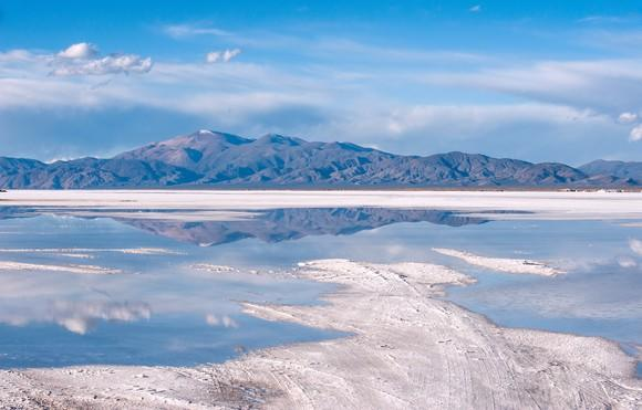 Lithium salt flats with a mountain and blue sky in the background.