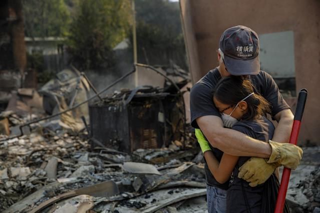 <p>Jeff Lipscomb assures his daughter Rachel Lipscomb, 11, that everything will be ok and that the family will pull through, as they survey their destroyed home after a brush fire on Dec. 6, 2017 in Ventura, Calif. (Photo: Marcus Yam/Los Angeles Times via Getty Images) </p>