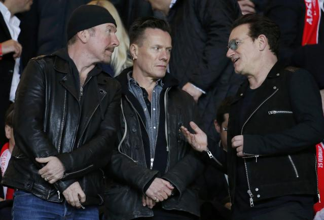 Members of the U2 band, from L-R, the Edge, Larry Mullen and Bono, are seen in the public ahead of the Champions League round of 16 second leg match where AS Monaco plays Arsenal at the Louis II Stadium in Monaco, March 17, 2015. REUTERS/Eric Gaillard (MONACO - Tags: SPORT SOCCER ENTERTAINMENT)