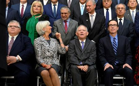 IMF Managing Director Christine Lagarde (2nd L) greets Pakistan's Finance Minister Muhammad Ishaq Dar as (seated, L-R) Mexico's Finance Minister Agustin Carstens, German Finance Minister Wolfgang Schauble and U.S. Treasury Secretary Steven Mnuchin take their seats for a family photo for the International Monetary and Financial Committee (IMFC), as part of the IMF and World Bank's 2017 Annual Spring Meetings, in Washington, U.S., April 22, 2017.   REUTERS/Mike Theiler