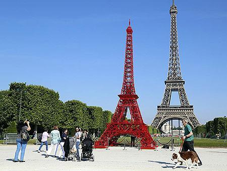 FRANCE: People stop to observe a replica of the Eiffel Tower built with red bistro chairs to mark the 125th anniversary of the Fermob company's bistro chairs in Paris June 24, 2014. Like the Eiffel Tower, the famous bistro chairs celebrate their 125th anniversary this year.