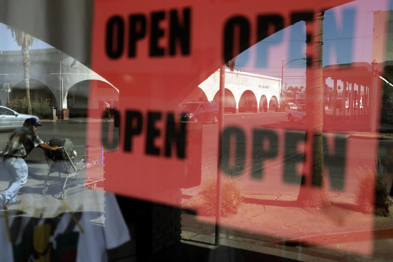 A man passes a clothing shop with open signs in the window, Tuesday, June 30, 2020, in Calexico, Calif. Saddled with a surge in positive cases and hospitalizations for the new coronavirus, a farming region on California's border with Mexico is now forced to backpedal on reopening its battered economy. The Imperial County board of supervisors unveiled a plan late Monday that includes closing businesses deemed non-essential, except for curbside pickup, and shuttering county parks. (AP Photo/Gregory Bull)