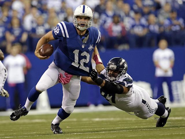 Seattle Seahawks defensive tackle Jordan Hill, right, tries to bring down Indianapolis Colts quarterback Andrew Luck during the second half of an NFL football game in Indianapolis, Sunday, Oct. 6, 2013. (AP Photo/AJ Mast)