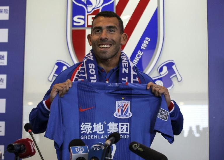 This file photo taken on January 21, 2017 shows Argentine striker Carlos Tevez posing with a jersey of his new club Shanghai Shenhua during a press conference in Shanghai on January 21, 2017. The Chinese Super League will take another step towards global recognition when it returns on March 3, 2017, boasting the world's richest players and a growing audience including live broadcasts in Britain. When Argentina's Carlos Tevez makes his league debut for Shanghai Shenhua, fans from Liaoning to Liverpool can tune in to see what can be bought with reported wages of 768,000 USD a week