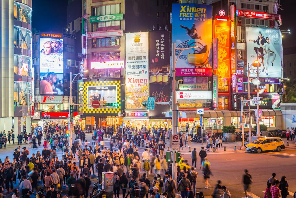 View across the crowded crossroads of Ximending past zooming traffic, shoppers and tourists enjoying the warm night illuminated by the colourful billboards and neon lights of Taipei's downtown commercial district, Taiwan.