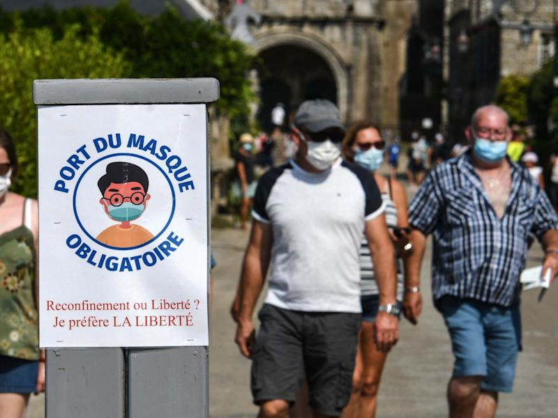 People wear protective face and nose masks as they stroll along a street in Locronan, western France: AFP via Getty Images