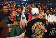 Canelo Alvarez hugs his girlfriend, Fernanda Gomez as their daughter, Maria, left, looks on, after defeating Billy Joe Saunders in a unified super middleweight world championship boxing match, Saturday, May 8, 2021, in Arlington, Texas. (AP Photo/Jeffrey McWhorter)