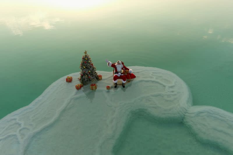 An aerial view shows Issa Kassissieh, wearing a Santa Claus costume, and sitting next to a Christmas tree while posing for a picture on a salt formation in the Dead Sea, near Ein Bokeq
