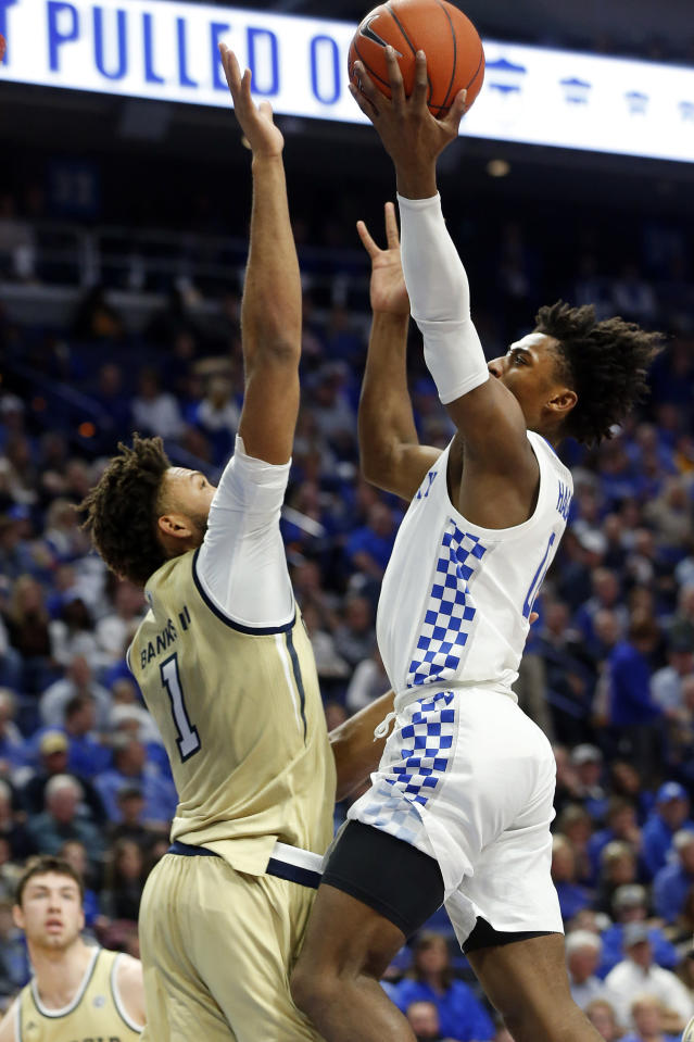 Kentucky's Ashton Hagans, right, shoots while pressured by Georgia Tech's James Banks III, left, during the first half of an NCAA college basketball game in Lexington, Ky., Saturday, Dec. 14, 2019. (AP Photo/James Crisp)