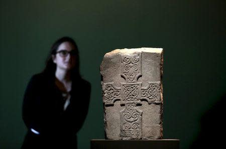 """A British Museum employee poses with a carved stone cross originating from Shetland, Scotland and made around AD 750-850, displayed in the """"Celts: art and identity"""" exhibition at the British Museum in London, Britain in this September 23, 2015 file photo. REUTERS/Suzanne Plunkett/Files"""