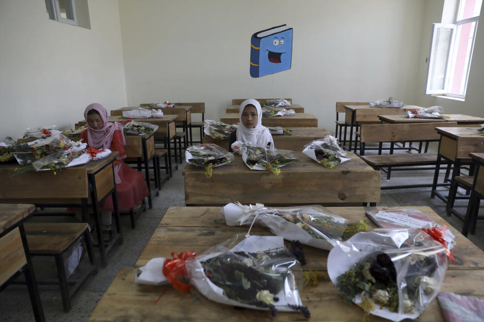 Schoolgirls sit inside a classroom with bouquets of flowers on empty desks as a tribute to those killed in the brutal May 8 bombing of the Syed Al-Shahda girls school, in Kabul, Afghanistan, Sunday, May 16, 2021. On Sunday parents of scores of young girls killed in the bombing demonstrated in the mostly Shiite neighborhood of Dasht-e-Barchi to demand the government provide them with greater security. They said 90 people were killed. (AP Photo/Rahmat Gul)