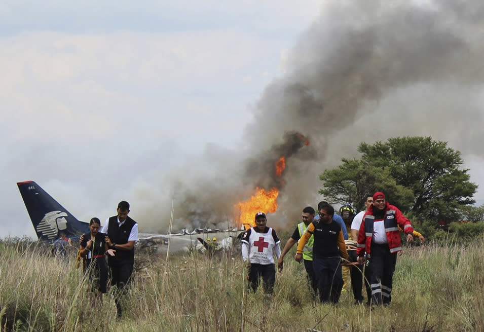 <p>In this photo released by Red Cross Durango communications office, Red Cross workers and rescue workers carry an injured person on a stretcher, right, as airline workers, left, walk away from the site where an Aeromexico airliner crashed in a field near the airport in Durango, Mexico, Tuesday, July 31, 2018. The jetliner crashed while taking off during a severe storm, smacking down in a field nearly intact then catching fire, and officials said it appeared everyone on board escaped the flames. (Photo: Red Cross Durango via AP) </p>