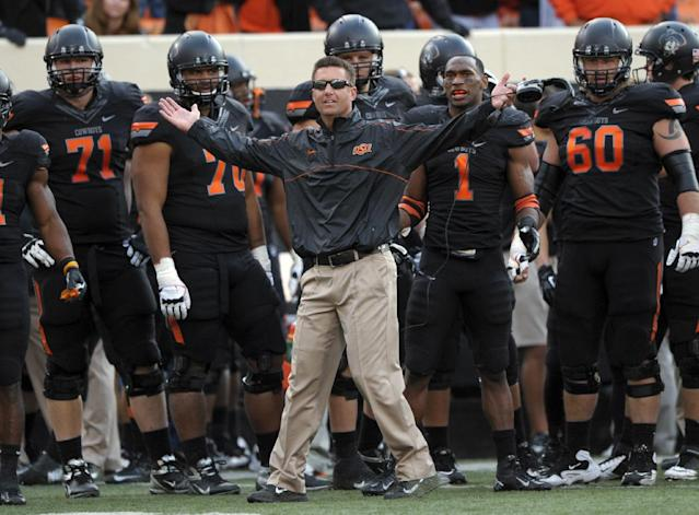 """FILE - In this Oct. 27, 2012, file photo, Oklahoma State coach Mike Gundy, center, questions an official's call denying Oklahoma State a touchdown during the second half of an NCAA college football game against TCU in Stillwater, Okla. An NCAA committee passed a proposal Wednesday, Feb. 12, 2014, that would allow defenses time to substitute between plays by prohibiting offenses from snapping the ball until 29 seconds are left on the 40-second play clock. """"The 10-second rule is like asking basketball to take away the shot clock - Boring!"""" Gundy tweeted Thursday. """"It's like asking a blitzing linebacker to raise his hand."""" (AP Photo/Brody Schmidt, File)"""