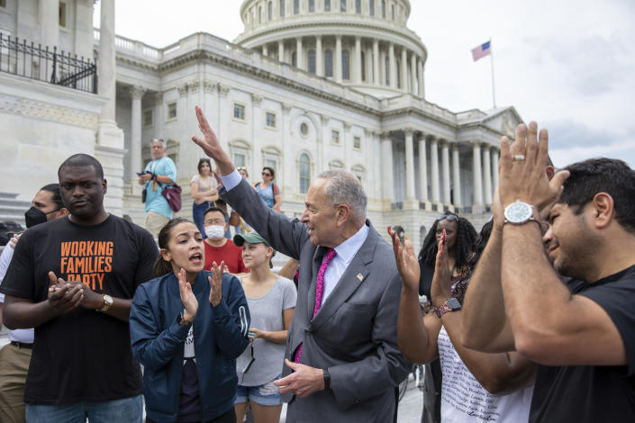From left, Rep. Mondaire Jones, D-N.Y., Rep. Alexandria Ocasio-Cortez, D-N.Y. and Senate Majority Leader Chuck Schumer, D-N.Y., celebrate the announcement that the Biden administration will enact a targeted nationwide eviction moratorium outside of Capitol Hill in Washington on Tuesday, Aug. 3, 2021. (AP Photo/Amanda Andrade-Rhoades)