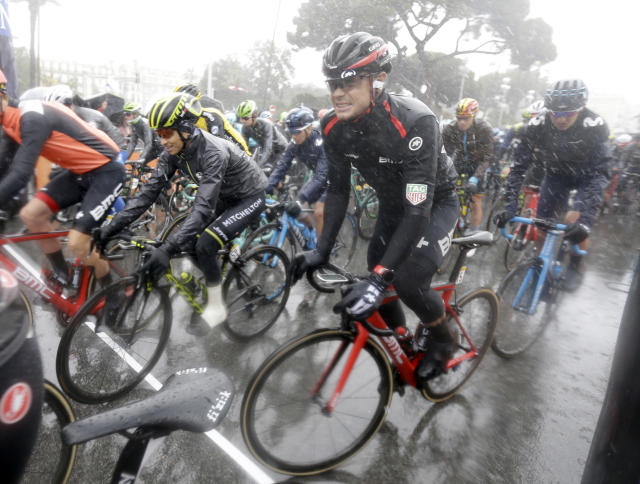 The pack of cyclists ride in the rain at the start of the eighth stage of the Paris-Nice cycling race between Nice and Nice in Nice, southeastern France, Sunday, March 11, 2018. (AP Photo/Claude Paris)