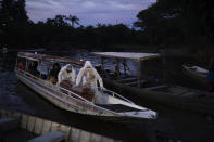 FILE - In this May 14, 2020 file photo, SOS Funeral workers transport by boat the coffin containing the body of a suspected COVID-19 victim that died in a river-side community near Manaus, Brazil. Navigating complex waterways to reach remote communities in Brazil's Amazon is only the first challenge for health workers vaccinating Indigenous and riverine people against COVID-19. Upon arrival, they face something they never anticipated: people refusing to take the shot. (AP Photo/Felipe Dana, File)