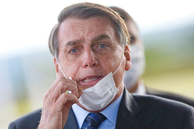 Brazil's President Jair Bolsonaro adjusts his mask as he leaves Alvorada Palace, amid the coronavirus disease (COVID-19) outbreak in Brasilia, Brazil May 13.