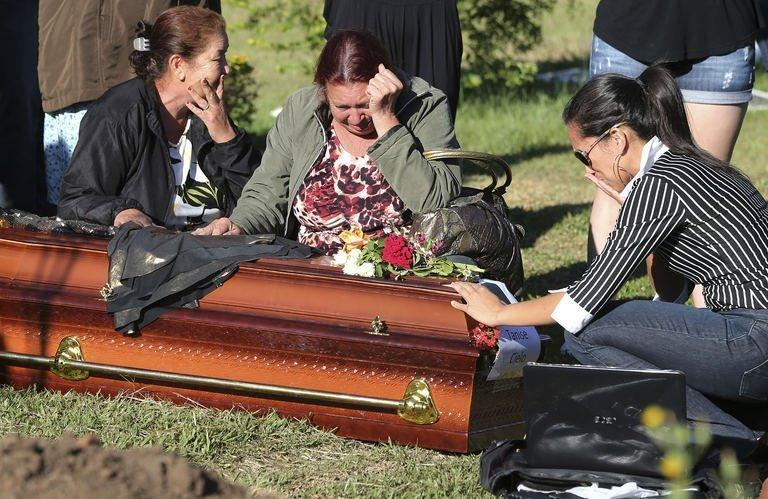 Relativies and friends of Tamise Cielo, one of the victims of the Kiss night club fire, gather around her coffin during the funeral at Santa Rita cementery in Santa Maria, on January 28, 2013. Police have arrested four suspects after the nightclub fire killed 231, left dozens more clinging to life and forced officials to defend readiness for the Olympics and World Cup