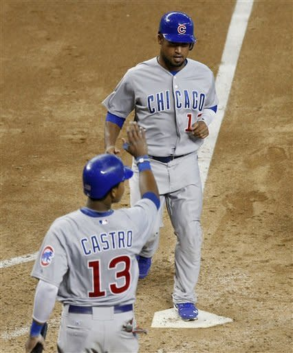 Chicago Cubs' Starlin Castro (13) and Dave Sappelt (17) score on a pinch-hit single by Bryan LaHair during the sixth inning against the Arizona Diamondbacks in a baseball game Sunday, Sept. 30, 2012, in Phoenix. (AP Photo/Rick Scuteri)