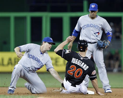 Miami Marlins' Justin Ruggiano (20) is tagged out at second base by Toronto Blue Jays second baseman Kelly Johnson, left, as Yunel Escobar backs up the play, after Ruggiano was caught off first in the second inning of an interleague baseball game in Miami, Friday, June 22, 2012. (AP Photo/Alan Diaz)