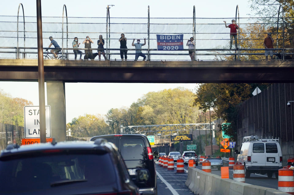 People watch the motorcade of President Donald Trump as it rolls through Arlington, Va., heading back to the White House, Saturday, Nov. 7, 2020. (AP Photo/Evan Vucci)