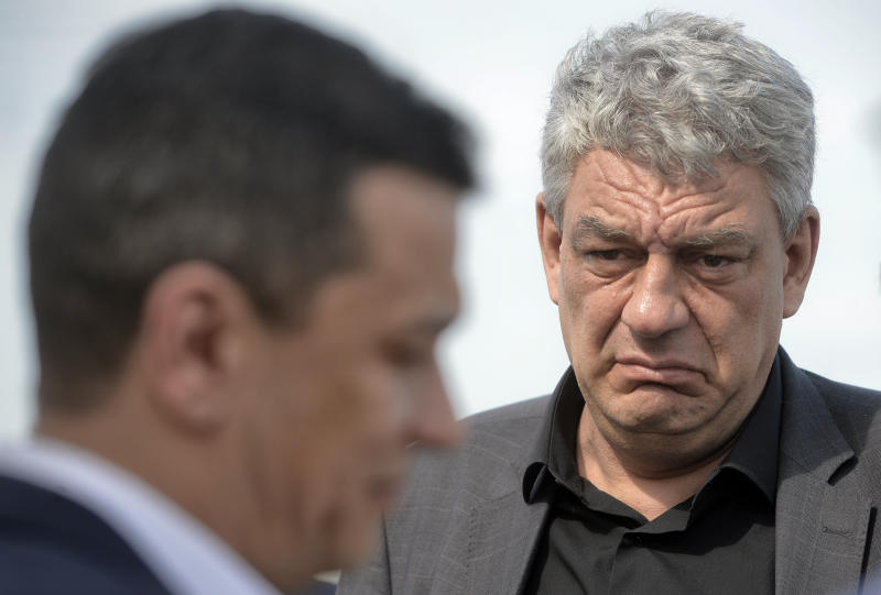 In this photo taken on May 12, 2017, economy minister Mihai Tudose, right, looks at former prime minister Sorin Grindeanu in Caravelle, Romania. The Social Democratic Party announced its choice for prime minister, lawmaker Mihai Tudose, 50-year-old economy minister in the previous government and an ally of Liviu Dragnea, the powerful leader of Romania's biggest political party. (AP Photo/Andreea Alexandru)