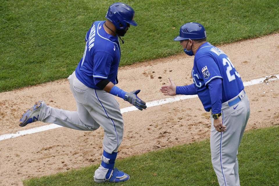 Kansas City Royals' Carlos Santana, left, rounds the bases as he celebrates with third base coach Vance Wilson after hitting a solo home run during the ninth inning of a baseball game against the Chicago White Sox in Chicago, Sunday, April 11, 2021. (AP Photo/Nam Y. Huh)