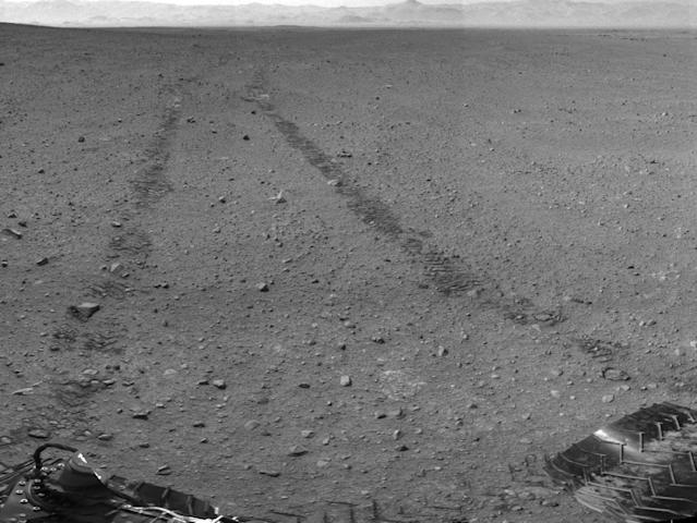 This handout photo provided by NASA/JPL-Caltech shows the surroundings of the location where NASA Mars rover Curiosity arrived on Sept. 4, 2012. It is a mosaic of images taken by Curiosity's Navigation Camera (Navcam) following the Sol 29 drive of 100 feet. Tracks from the drive are visible in the image. For scale, Curiosity leaves parallel tracks about 9 feet apart. The rover Curiosity is making its mark on Mars. Its tracks are big enough to be seen from space. In just one month, the car-sized rover has driven 368 feet on the red planet. That's slightly more than the length of a football field. Curiosity's slightly zig-zaggy tire tracks were photographed from a NASA satellite circling Mars and also from the rover's rear-facing cameras. Curiosity landed on Aug. 5. (AP Photo/NASA/JPL-Caltech) The panorama is centered to the north-northeast, with south-southwest at both ends.
