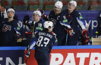 Conor Garland of the US, center, celebrates with teammates after scoring his side's sixth goal during the Ice Hockey World Championship quarterfinal match between the United States and Slovakia at the Arena in Riga, Latvia, Thursday, June 3, 2021.(AP Photo/Sergei Grits)