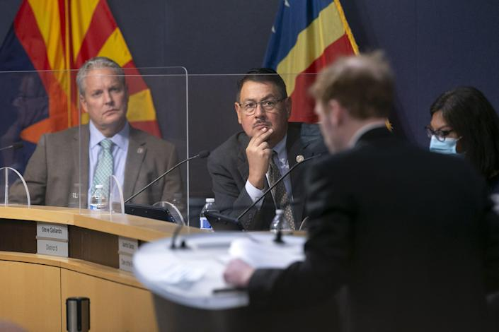 Clint Hickman, left, and Steve Gallardo, center, both  supervisors of the Maricopa County Board of Supervisors, listen as Maricopa County Recorder Stephen Richer speaks during a Maricopa County Board of Supervisors meeting about the Senate Audit of Maricopa County ballots from the 2020 general election, at the Maricopa County government complex in Phoenix on May 17, 2021.