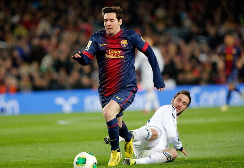 Barcelona's Lionel Messi, from Argentina, left, escapes Real Madrid's Gonzalo Higuain, also from Argentina, during the Copa del Rey soccer match between FC Barcelona and Real Madrid in Barcelona, Spain, Tuesday, Feb. 26, 2013. (AP Photo/Emilio Morenatti)