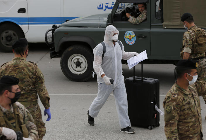 A Lebanese passenger who was stuck in Saudi Arabia wears a protective suit as he passes Lebanese soldiers after arriving to Rafik Hariri Airport, in Beirut, Lebanon, Sunday, April 5, 2020. A jet carrying more than 70 Lebanese citizens, who had been stuck in Saudi Arabia after Beirut's international airport closed nearly three weeks ago to limit the spread of coronavirus, arrived in Lebanon Sunday. The flight was the beginning of flights that aim to return thousands of Lebanese from around the world. (AP Photo/Hussein Malla)