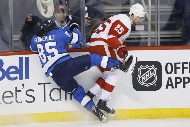 Winnipeg Jets' Mathieu Perreault (85) and Detroit Red Wings' Mike Green (25) collide during the first period of an NHL hockey game Friday, Jan. 11, 2019, in Winnipeg, Manitoba. (John Woods/The Canadian Press via AP)