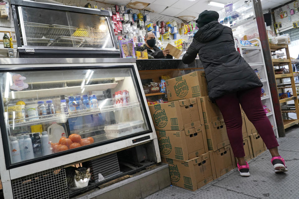 Bodega owner Frank Marte, left, serves a customer as his cat Ramon, lower left, sits beneath a display case, Wednesday, Feb. 10, 2021, in the Bronx borough of New York. Marte, who heads up the Bodega and Small Business Group, which represents bodegas in New York, said he's been lobbying local officials to set aside COVID-19 vaccine appointments for bodega workers, many of whom are unaware they are eligible. He hopes the recent opening of a large vaccination site at Yankee stadium will make access easier for people like him. (AP Photo/Kathy Willens)