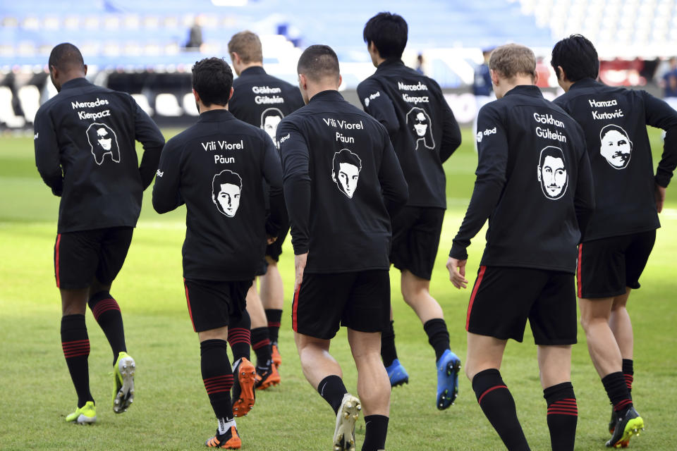 Frankfurt's players wear the pictures and names of the victims of the shooting in Hanau a year ago on their training jackets, prior to the German Bundesliga soccer match between Eintracht Frankfurt and Bayern Munich in Frankfurt, Germany, Saturday, Feb. 20, 2021. A right-wing extremist shot dead nine people in Hanau on 19 Feb. 2020, before shooting himself. (Arne Dedert/POOL via AP)