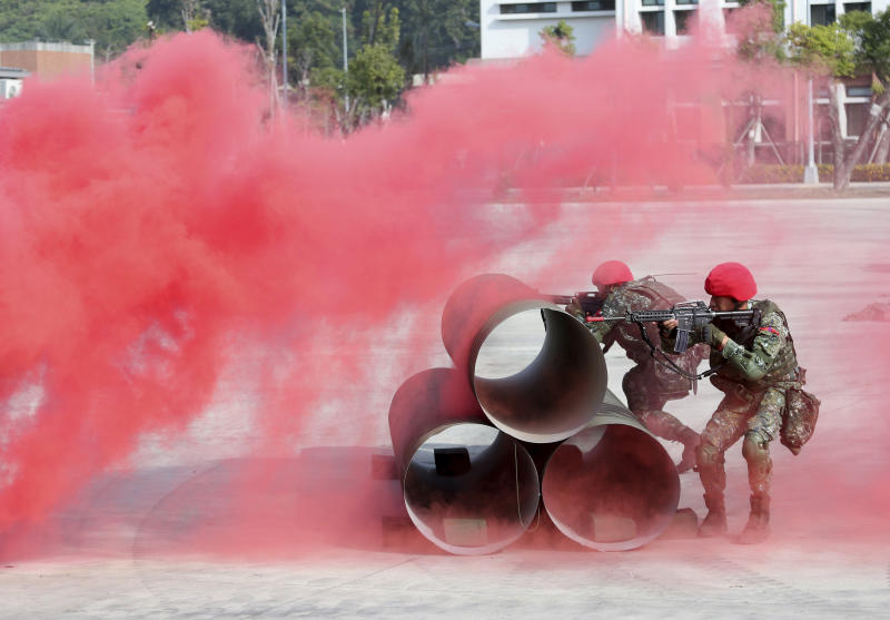 Two soldiers of fictitious enemy fire during a military exercise in Kaohsiung, southern Taiwan, Wednesday, Jan. 15, 2020. Taiwan military started a two-day joint forces exercises on Wednesday to show its determination to defend itself from Chinese threats. (AP Photo/Chiang Ying-ying)