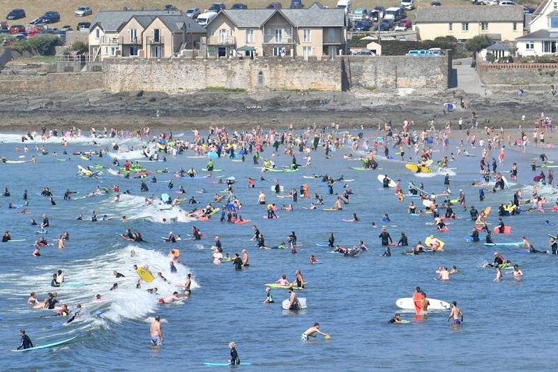 People in the sea at Croyde Beach in North Devon as another spell of warm weather hits the UK.