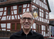 Thomas Metzmacher stands in front of his apple cider restaurant 'Zum Lahmen Esel' in Frankfurt, Germany, Friday, April 3, 2020. Due to the coronavirus outbreak the restaurant which has been in operation since 1807 offers cider and food to go in a self-made drive through set up. (AP Photo/Michael Probst)