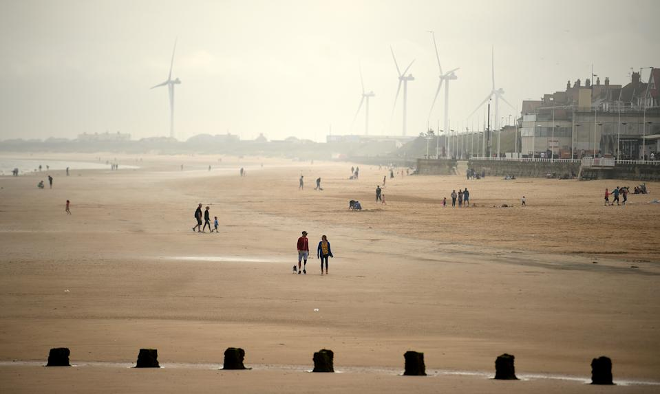 People walk and play on the beach and in the sea in Bridlington on the north east coast of England on June 15, 2020 following further relaxations in the novel coronavirus lockdown rules. (Photo by Oli SCARFF / AFP) (Photo by OLI SCARFF/AFP via Getty Images)