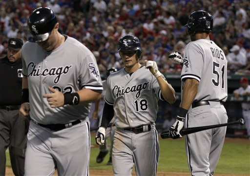 Chicago White Sox's Adam Dunn (32) and Brent Lillibridge (18) are congratulated by Alex Rios (51) after the two scored on a Paul Konerko double in the third inning of a baseball game off a pitch from Texas Rangers' Derek Holland, Saturday, April 7, 2012, in Arlington, Texas. (AP Photo/Tony Gutierrez)