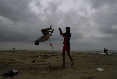 Boys practice somersaulting on a beach against the backdrop of pre-monsoon clouds in Kochi