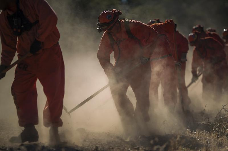 Inmate firefighters from Oak Glen Conservation Camp clear vegetation that could fuel a wildfire near a road (AFP Photo/DAVID MCNEW)